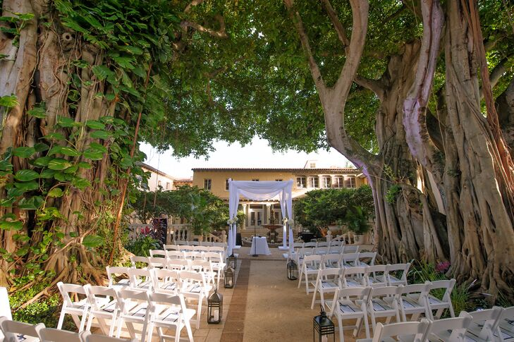 Melissa and Derek used the Addison's twin Banyan trees as the main decor for their wedding in Boca Raton, Florida. Rows of white folding chairs were met with navy fan programs as simple black lanterns lined the aisle. The couple's white fabric-draped chuppah stood out with the only florals along each post: white hydrangeas and roses.