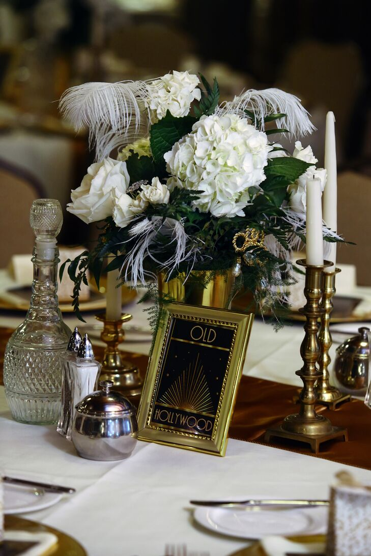 The centerpieces included white feathers and hydrangeas, taper candles and gold Old Hollywood table numbers.