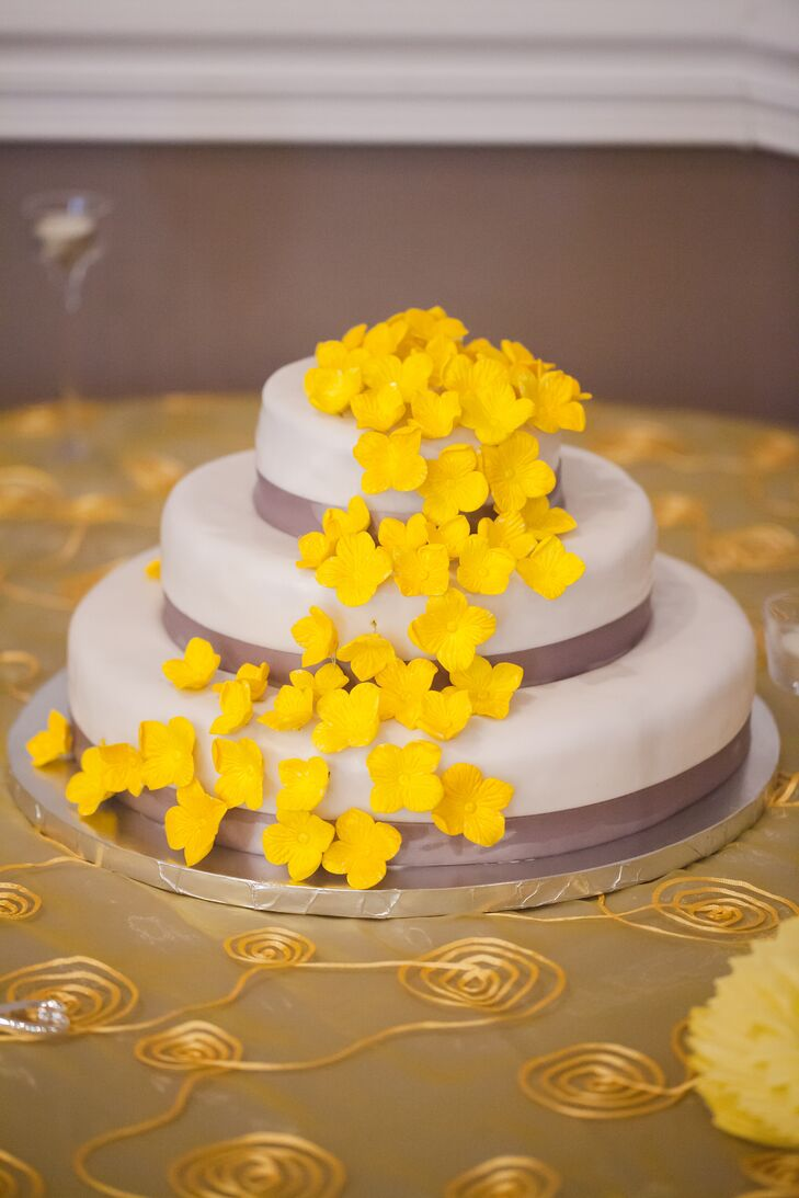 The low three-tier cake embodied the wedding's classic style and the yellow and gray palette. Yellow cake flowers draped down the side of the cake.
