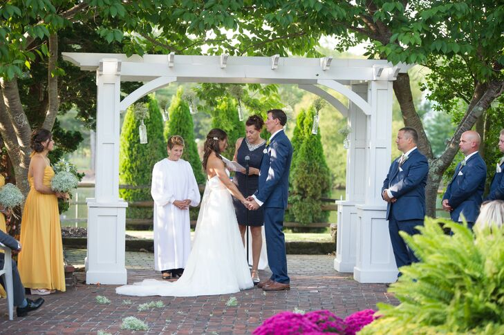 Karen and Todd said 'I do' under a simple white wooden wedding arch at The Colonial Inn in Smithville, New Jersey.