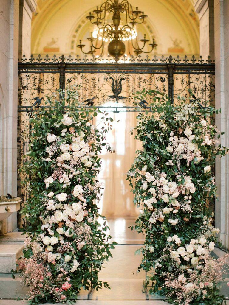 Dramatic lush floral bushes at wedding entrance