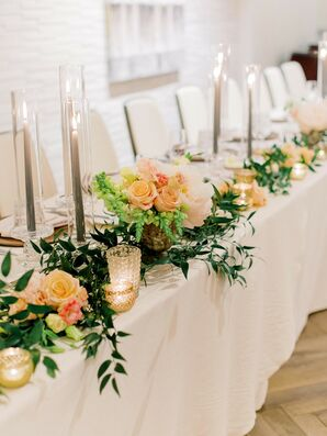 Romantic Head Table with Pink Flowers, Greenery Garland and Taper Candles in Glass Votives
