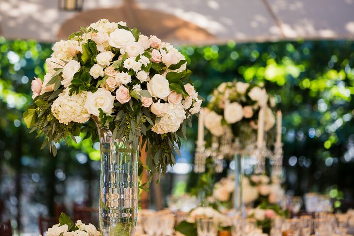 The elegant Sperry tent was awash with romantic shades of ivory, blush and pink hues taking on the form of ornate arrangements of garden roses, hydrangeas and lush greenery. Winston Flowers created three distinct arrangements to infuse the open-air space with drama and visual intrigue. Bouquets of the full florals cascaded from tall trumpet vases and crystal candelabras, as well as traditional low-footed vases that exuded timeless appeal.