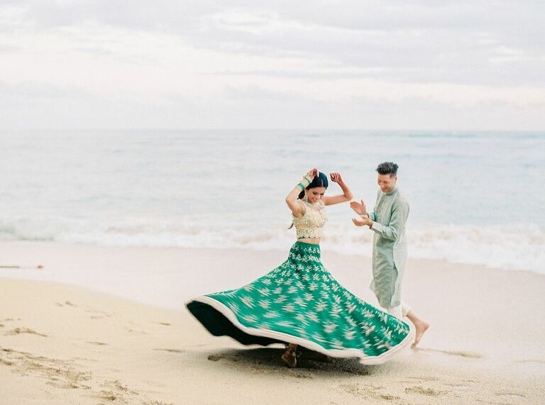 Bride twirling in wedding dress on the beach while groom claps
