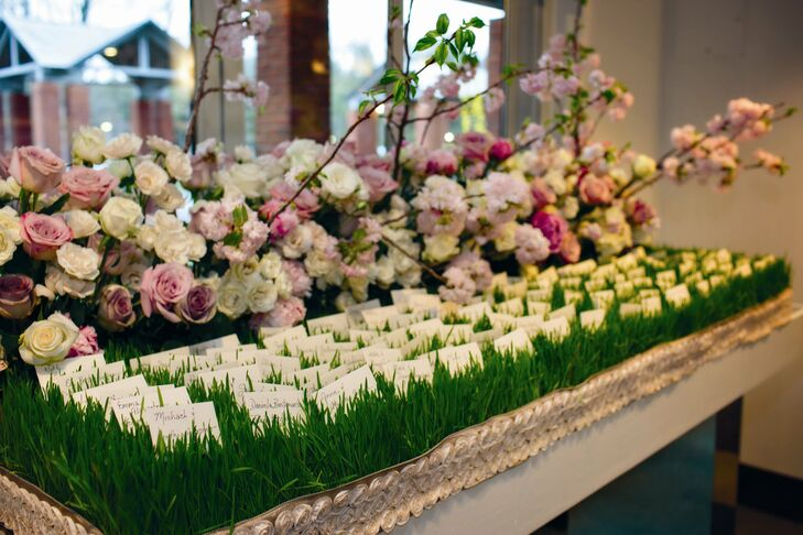 The escort cards were nestled in grass beds, adding a whimsical touch to the romantic garden decor.