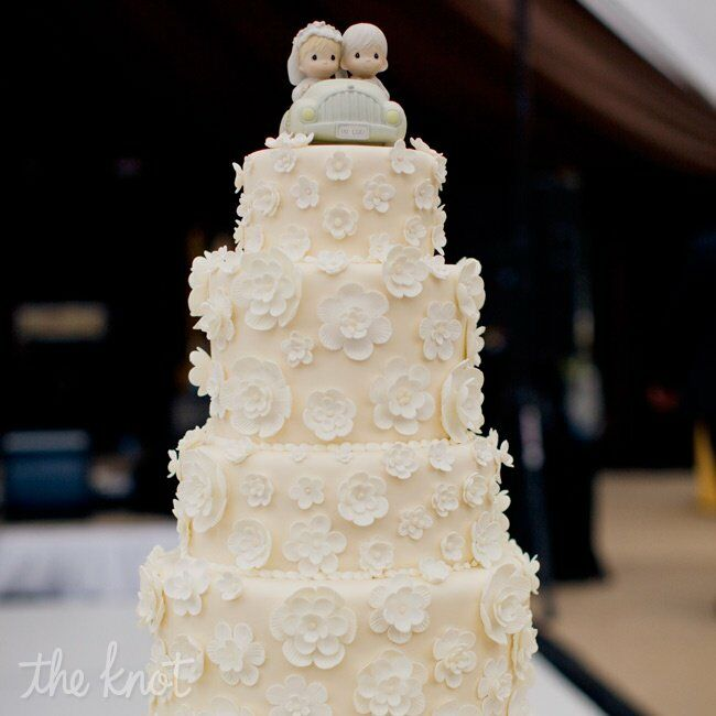 The four-tiered ivory cake was covered with mini fondant flowers.