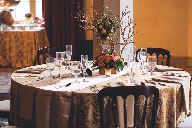 Inside the Don Room at El Cortez, dining tables in gold tablecloths were decorated with centerpieces of lush flower centerpieces on branches.