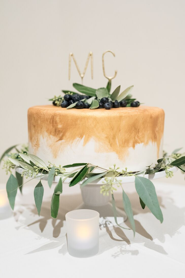 Tulie Bakery in Salt Lake City, Utah, crafted a gold and ivory almond cake, which was topped with the bride and groom's initials and eucalyptus leaves.