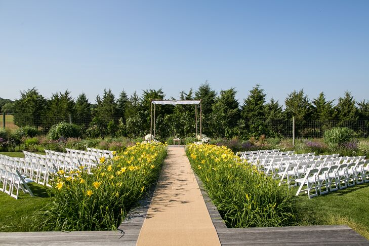 """The ceremony took place on Brad's parents' back deck overlooking a beautiful natural farm preserve in Southampton, New York. The aisle leading to the main platform, where Maria and Brad exchanged vows, was surrounded by sunny yellow lilies and lush green grasses that swayed gently in the wind. A birch chuppah was placed at the edge of the deck, topped with sheer white fabric and framed by French flower buckets filled with bright white blooms. """"It was an incredible setting and the weather that day could not have been more perfect,"""" Maria says. """"The bluest sky imaginable, no clouds and a beautiful sunset."""""""
