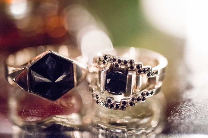 Lindsay's art deco-style ring centers on a single black diamond. Justin's ring resembles a fantasy villain's ring and is made with a hexagonal black onyx. Both rings were designed by New Zealand jeweler Meadowlark.