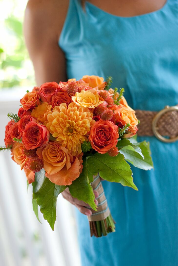 The four bridesmaids carried vibrant bouquets of dahlias and roses in shades of red and orange— complementary colors to their bold turquoise gowns