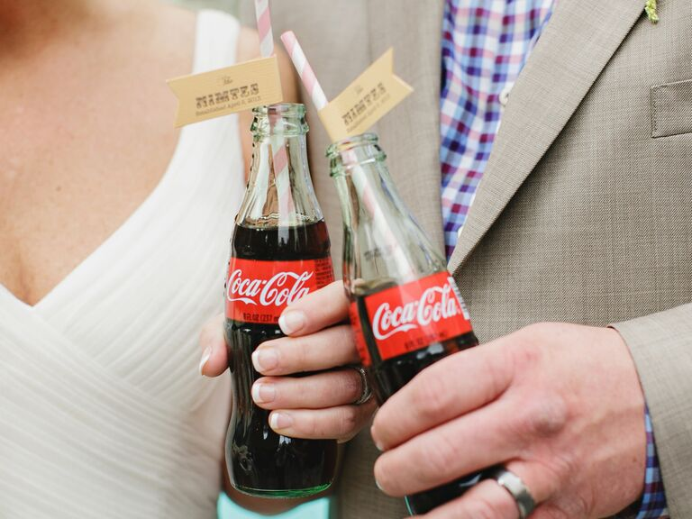 Bride and groom cheers with glass bottle cokes and striped paper straws