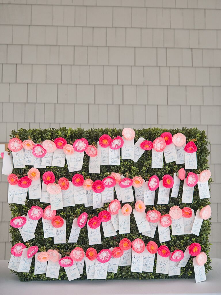 Bright pink paper flower escort card display