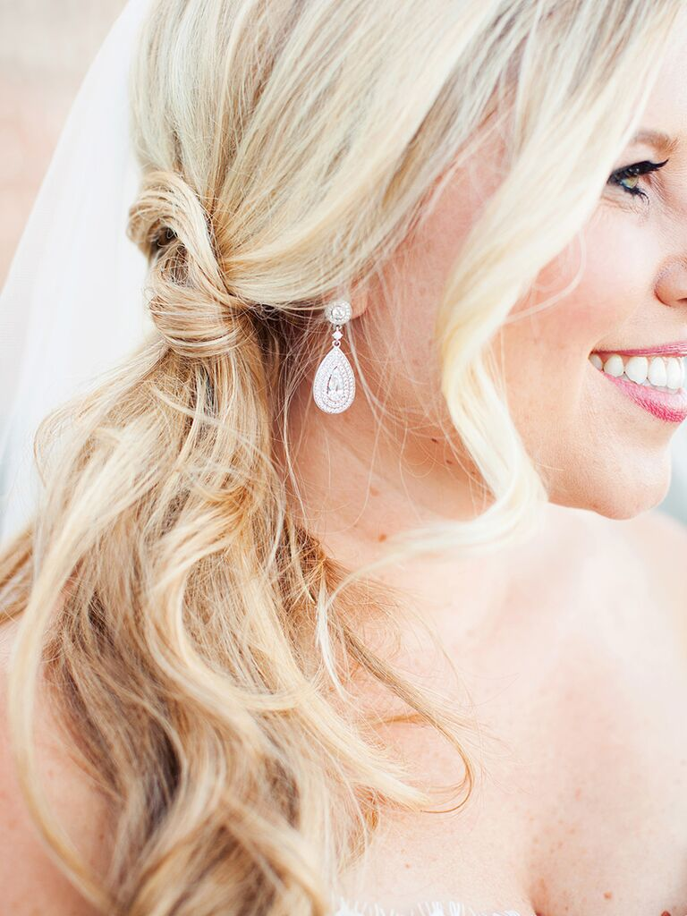 Long curly wedding hairstyle sideswept into a ponytail