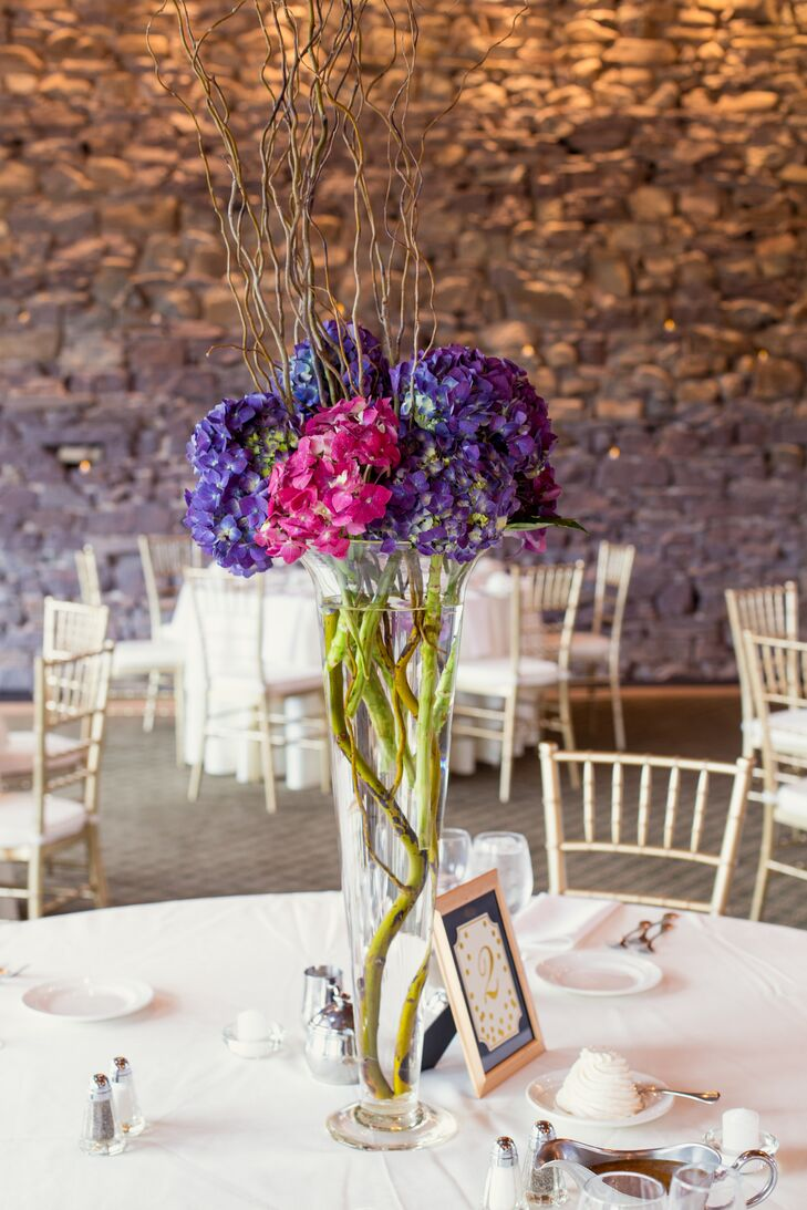The team at Chantilly Floral Boutique made eye-catching arrangements for the couple's reception and added a whimsical flair to the day. Purple hydrangeas were mixed with pink hydrangeas and two types of branches in tall trumpet of low cylinder vases. Each added an unexpected accent to the La Massaria at Bella Vista's exposed-brick walls.