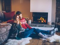 couple in holiday sweaters sitting by the fire