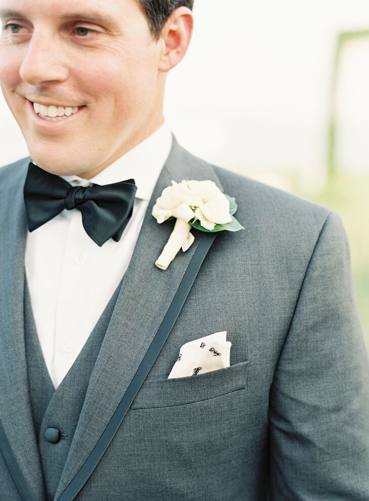 The groom sported a Black by Vera Wang dark gray slim-fit tuxedo, perfect for the couple's alfresco black-tie affair. Ryan accessorized with a simple garden rose boutonniere and light gray socks that were adorned with red and navy blue anchors, a nod to their nautical venue.
