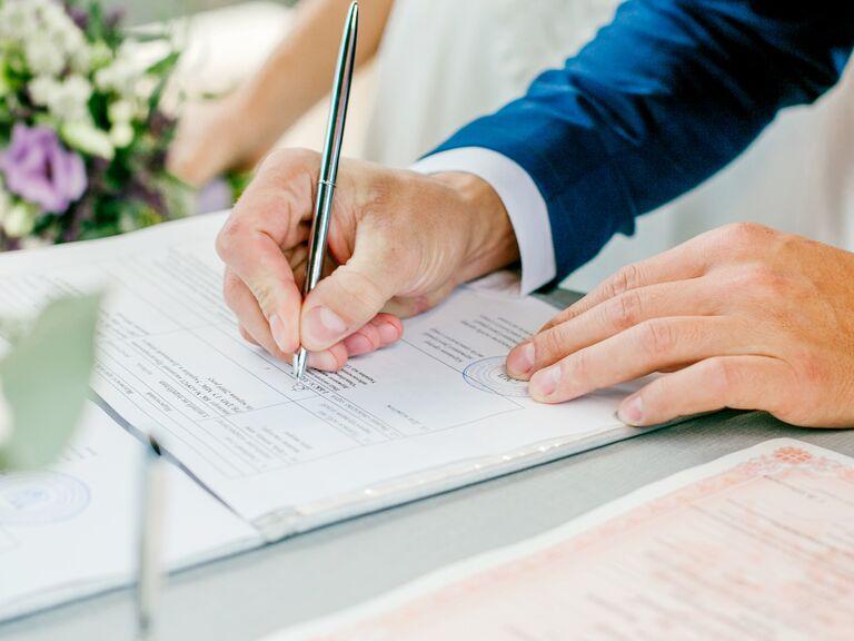 man signing marriage license