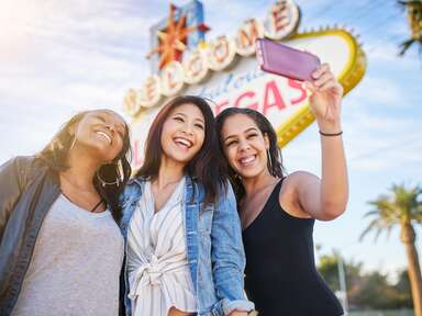 three women taking a selfie in front of the las vegas sign