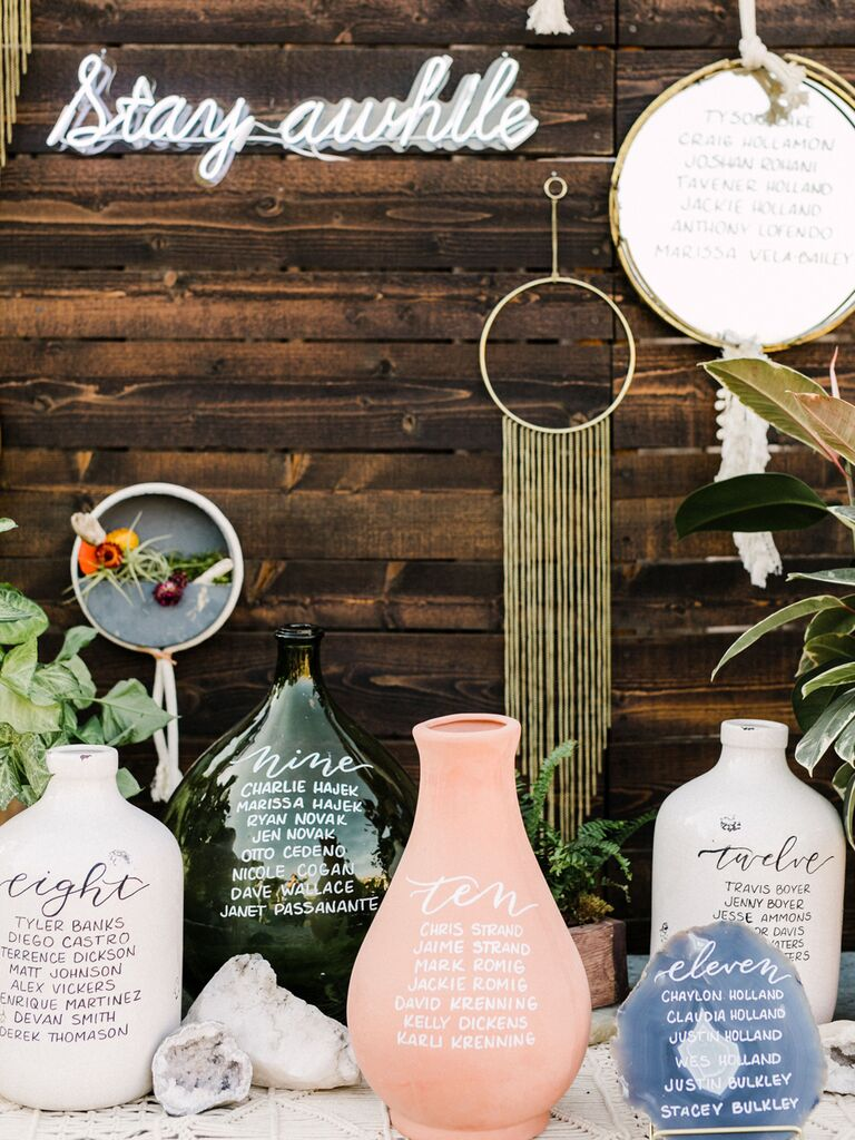 Bohemian wedding table arrangements on emerald, pink and white vases