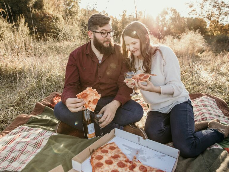 engagement photo shoot eating pizza on a picnic