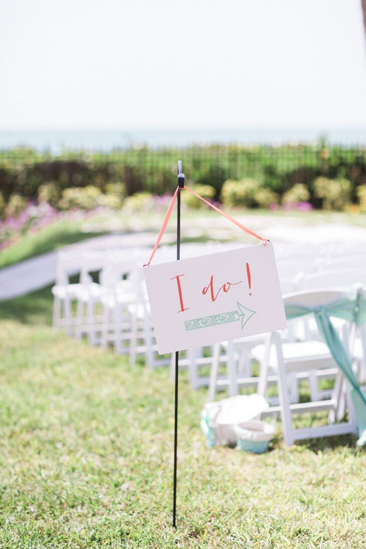 "Guests were pointed to the outdoor ceremony with a sweet sign. The accent brought out their coral and mint wedding colors with a calligraphy ""I do"" and intricate mint arrow that resembled the waves on their stationery."