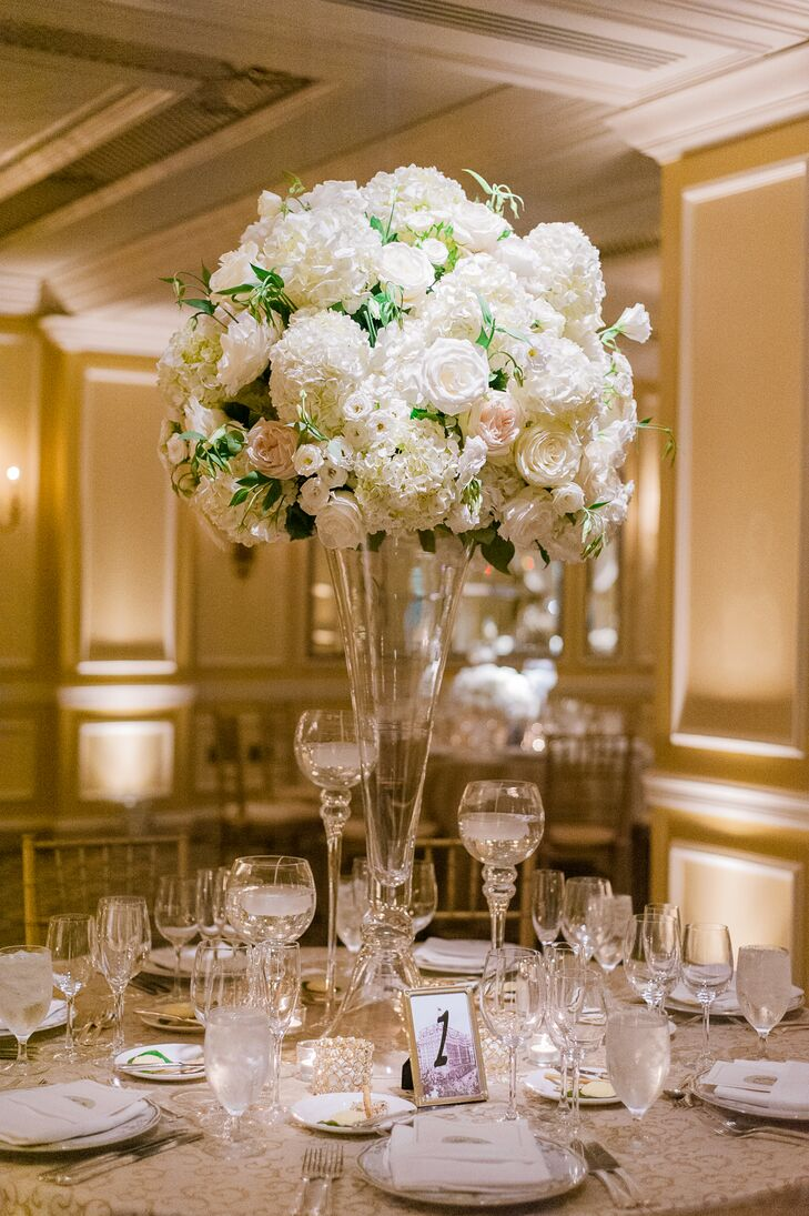Some dining tables at the reception were decorated with tall glass pilsner vases topped with dome-shape flower arrangements. The blush and ivory flower arrangements included hydrangeas, lisianthus and roses.