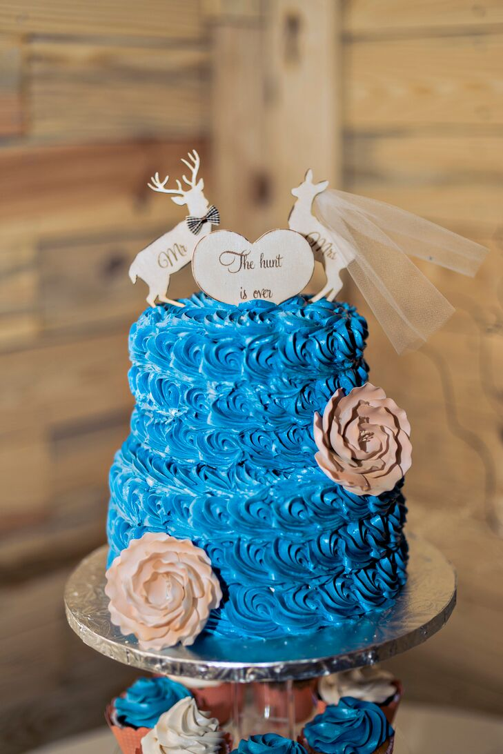 Chris's love of hunting inspired their two-tier cake, covered in bright blue buttercream rosettes.