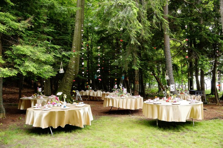 """Dinner and cocktail hour took place in a quaint clearing in the woods adjacent to Sarah's family home. The week before the wedding, Sarah's father, brothers and Luis worked hard to clear and level the ground to make it ready for the event, in addition to doing some preventive mosquito spraying the day before. """"I thought it turned out so magical, especially as the sun went down and all the lanterns and twinkle lights lit up,"""" Sarah says."""