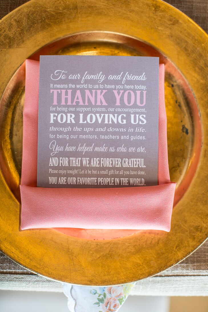 Gray stationery with white and pink text displayed a thank-you message for friends and family. Pink napkins bordered the cards, and the display sat on top of elegant gold charger plates.