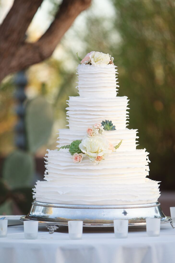 After dinner, Maggie and Joseph treated guests to a traditional slice of wedding cake. The couple's five-tiered confection featured thin layers of fondant that created a ruffled effect and clusters of fresh ivory and blush blooms.