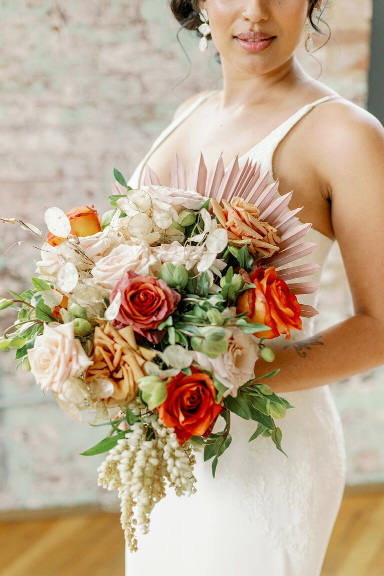 bohemian wedding bouquet showcasing 2021 wedding colors with orange roses greenery and pale pink sun palms