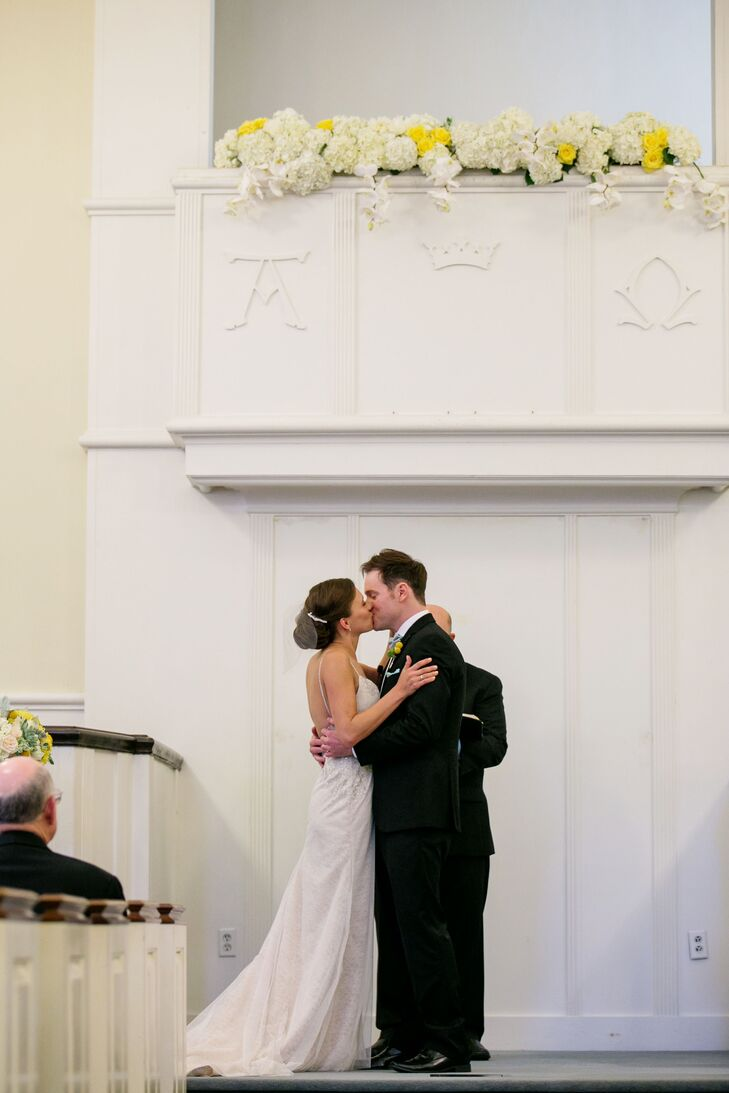 """At the Norfolk Church of Christ, Lindsey and Chris shared their first kiss as a married couple. They decorated the space with an orchid and hydrangea flower arrangement that hung from the altar, inspired by a scene from """"The Great Gatsby."""""""