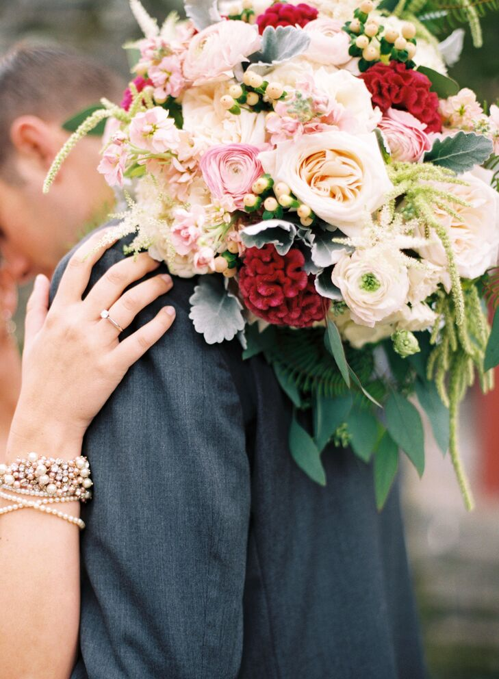Lauren carried a gorgeous bouquet with red coxcomb, pink and ivory ranunculus, blush and peach garden roses, dusty miller and hypericum.