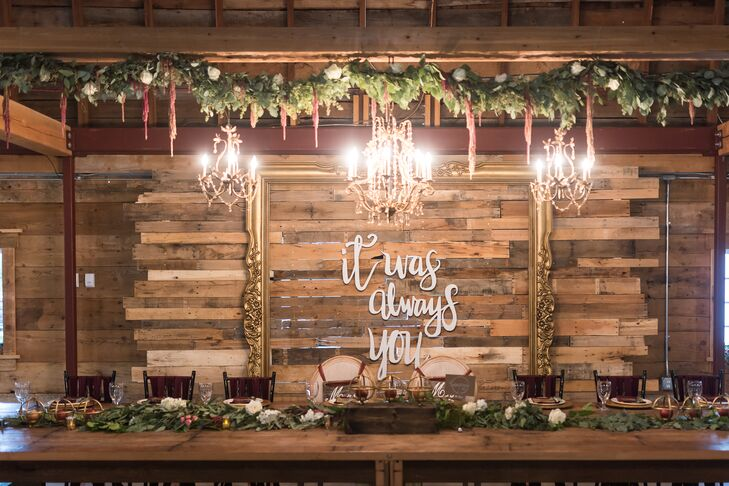 A verdant garland and custom chandelier installation framed the head table, creating a stunning overhead display.