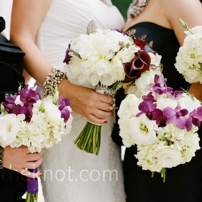 Textured bouquets of white and purple blooms were accented with spotted guinea feathers. Michelle's bouquet was wrapped in a crystal rosary passed down from her great-grandmother.