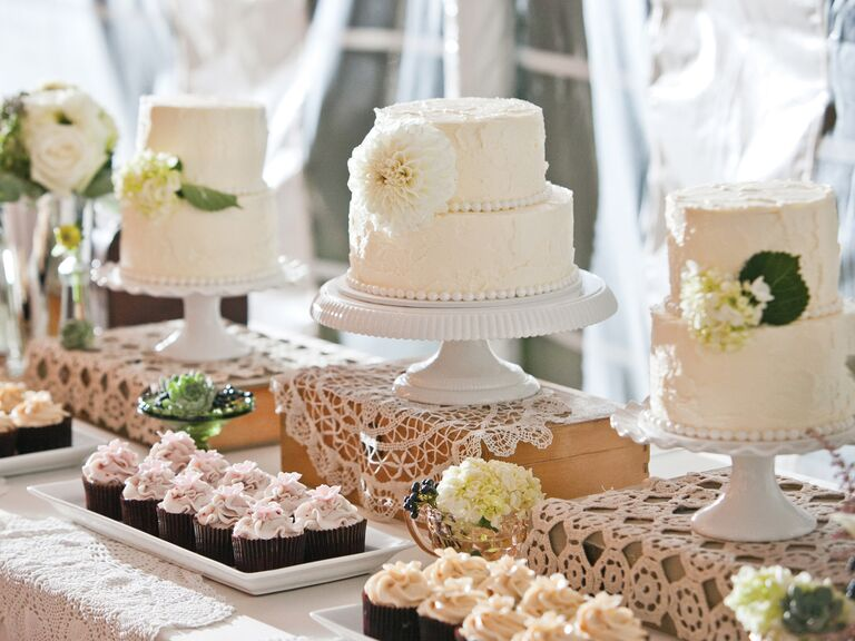 Tiered wedding cakes with flowers and cupcakes