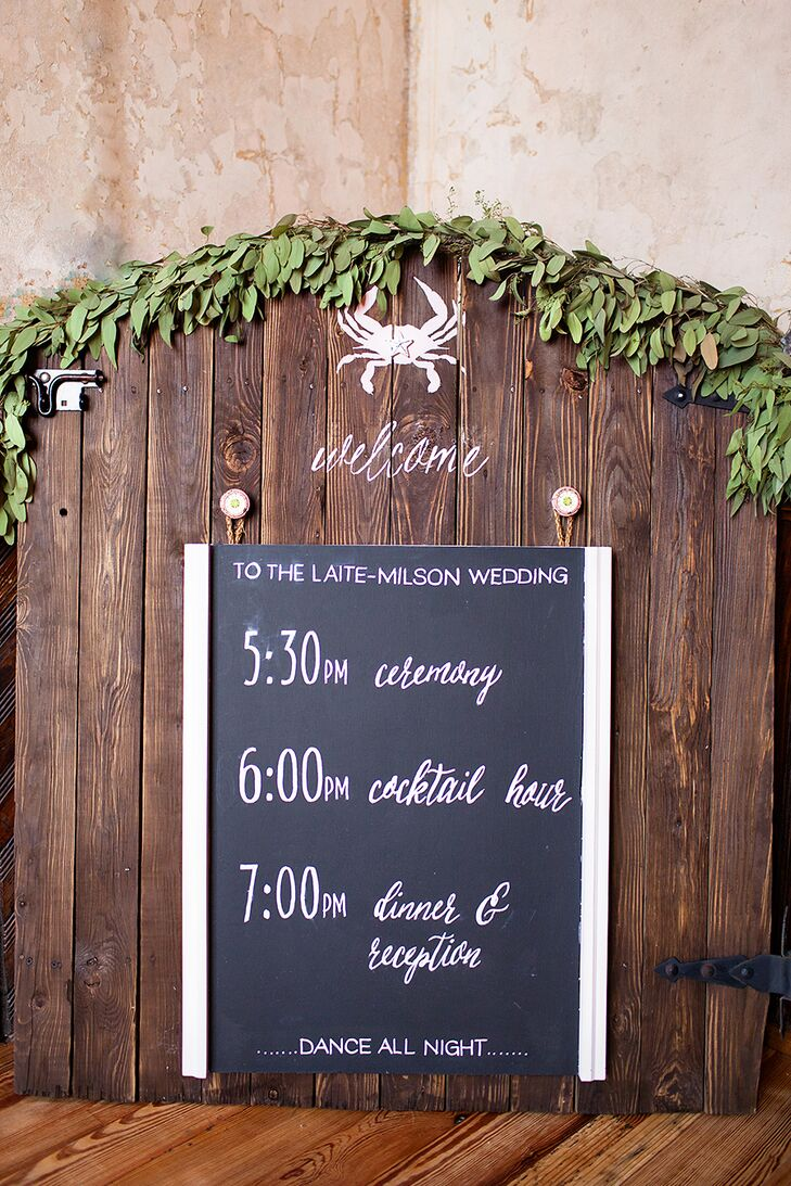 A handwritten chalkboard sign was used to give the guests a schedule for the night. It was hung rustic wood draped in fresh greenery, and as a tribute to Christi (a Maryland native) a little chalk crab was drawn on the top.