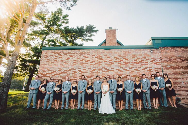 Navy blue tied together the wedding party look. The bridesmaids wore knee-length navy dresses with one-shoulder or sweetheart necklines. The groomsmen wore classic gray three-piece suits and striped navy and white ties to match the girls' look.