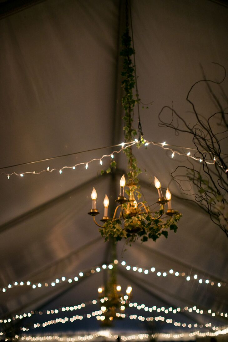 Inside the reception tent at Woolverton Inn in Stockton, New Jersey, rows of string lights added whimsical ambiance. A number of chandeliers ran along the center of the tent and were decorated with ivy.