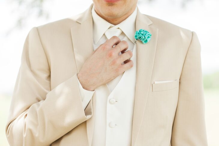 Tarik tied their wedding color, one of Cami's favorite colors, into his look with a single accent. A Tiffany blue rosette served as a boutonniere on the lapel of his neutral suit from Men's Wearhouse. His groomsmen wore matching Tiffany blue vests for some extra color.
