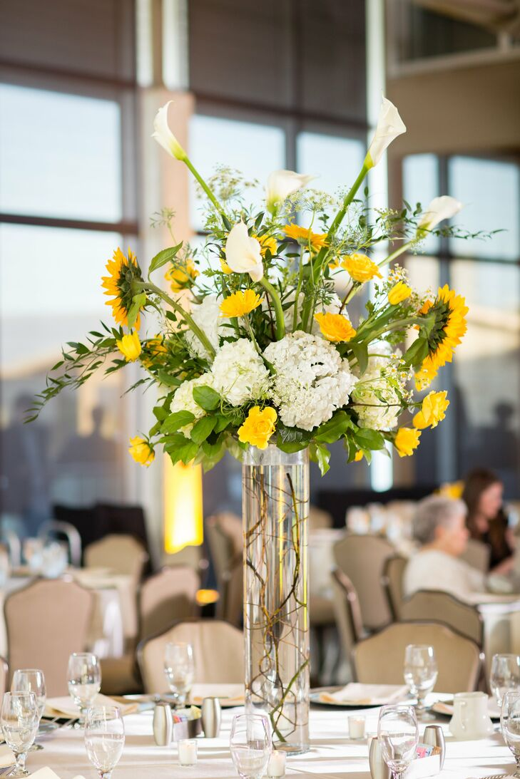 A variety of centerpieces topped tables, including tall clear vases of sunflowers, tulips, roses, hydrangeas and calla lilies.