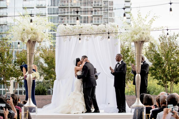 Angela and Nicholas's traditional Christian ceremony incorporated scripture readings, a sand ceremony and a jazz trio and vocalist. The bride's cousin, an ordained minister, officiated the ceremony on the patio of the Four Seasons, which overlooked downtown Atlanta, Georgia.