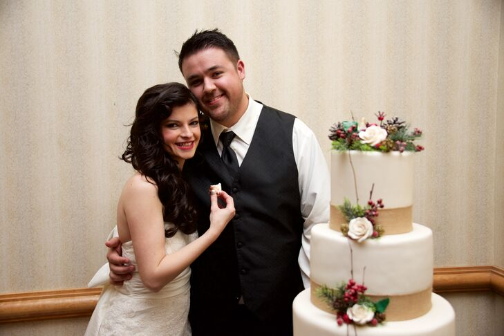 Camelia and Simon had a wintery wedding cake decorated with white roses, red berries and pinecones.