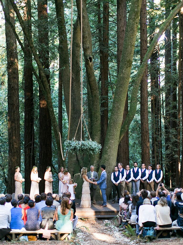 Whimsical outdoor wedding ceremony with a suspended chandelier