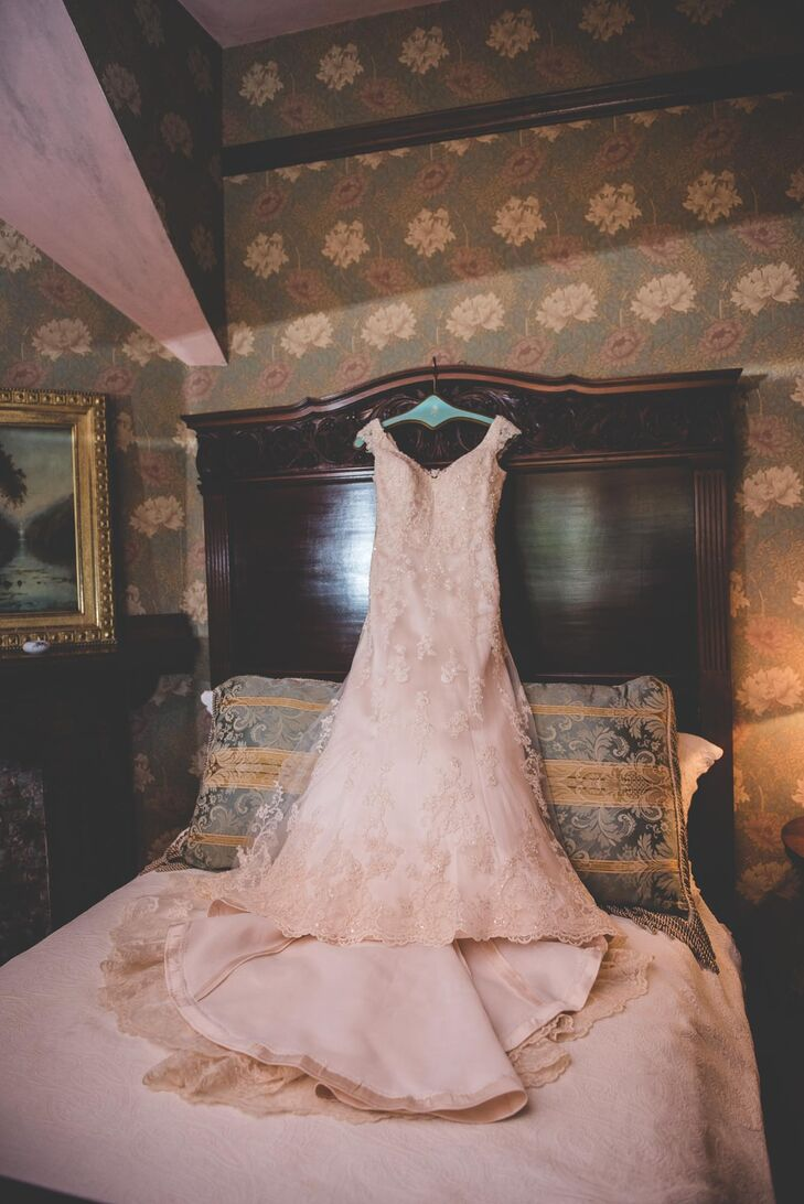"""The bride wore a Maggie Sottero lace wedding dress with a tulle skirt. The A-line gown was finished with illusion lace cap-sleeves and illusion neckline. """"I liked the vintage look of it, and the fact that it was slightly gold in color,"""" Katie says."""
