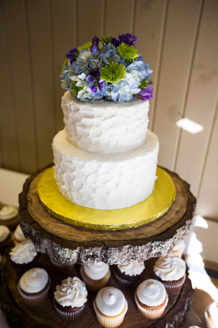 The two-tiered ivory cake was topped with blue and purple floral decor, and sat above an assortment of cupcakes. The cupcake flavors ranged from black bottom, almond and carrot.