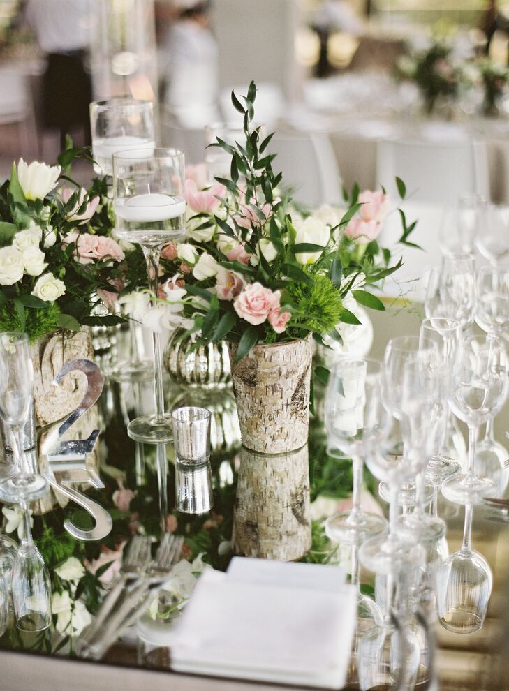 After the cocktail hour, guests moved outside to the museum's large patio for the reception, where multiple tables surrounded a large dance floor framed by the hanging gardens. The tables were decorated with mirrored tops, white, blush, and green flowers and white candles.
