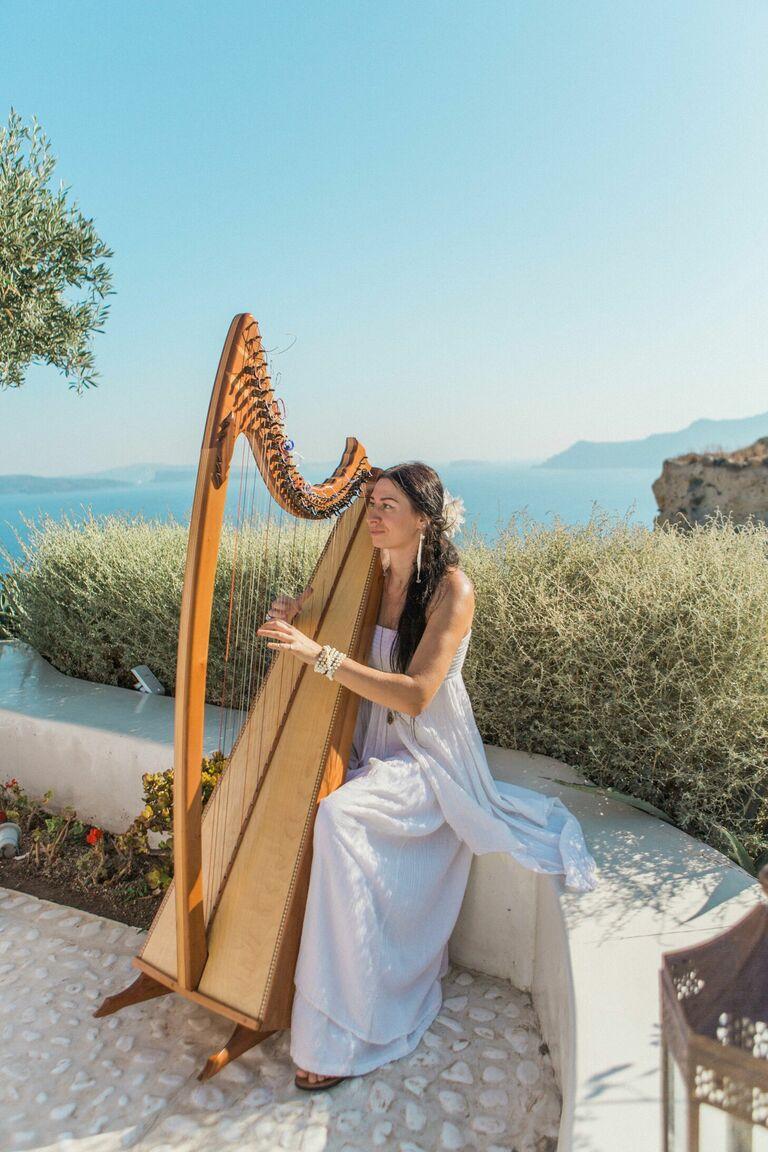 Woman playing harp at oceanside wedding