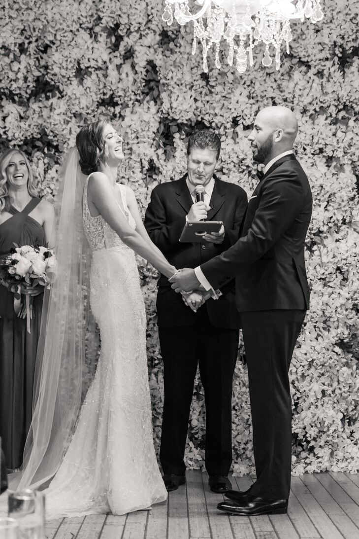 Vow Exchange in Front of a Flower Wall
